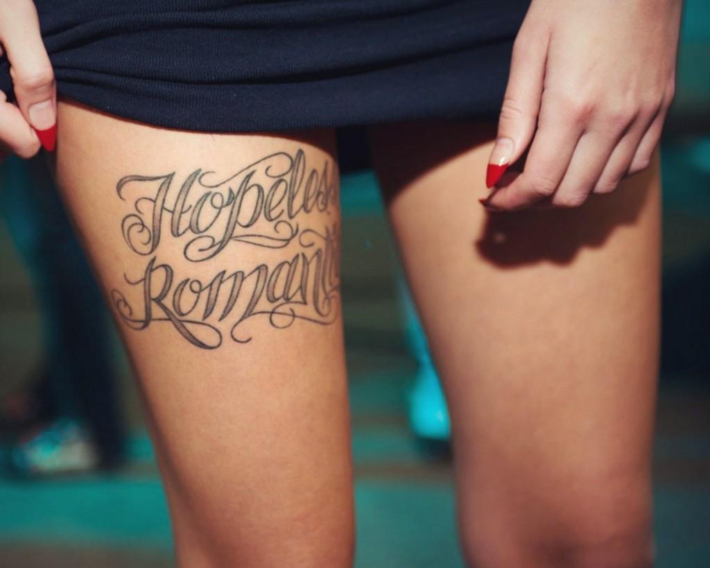 Женская татуировка надпись на бедре