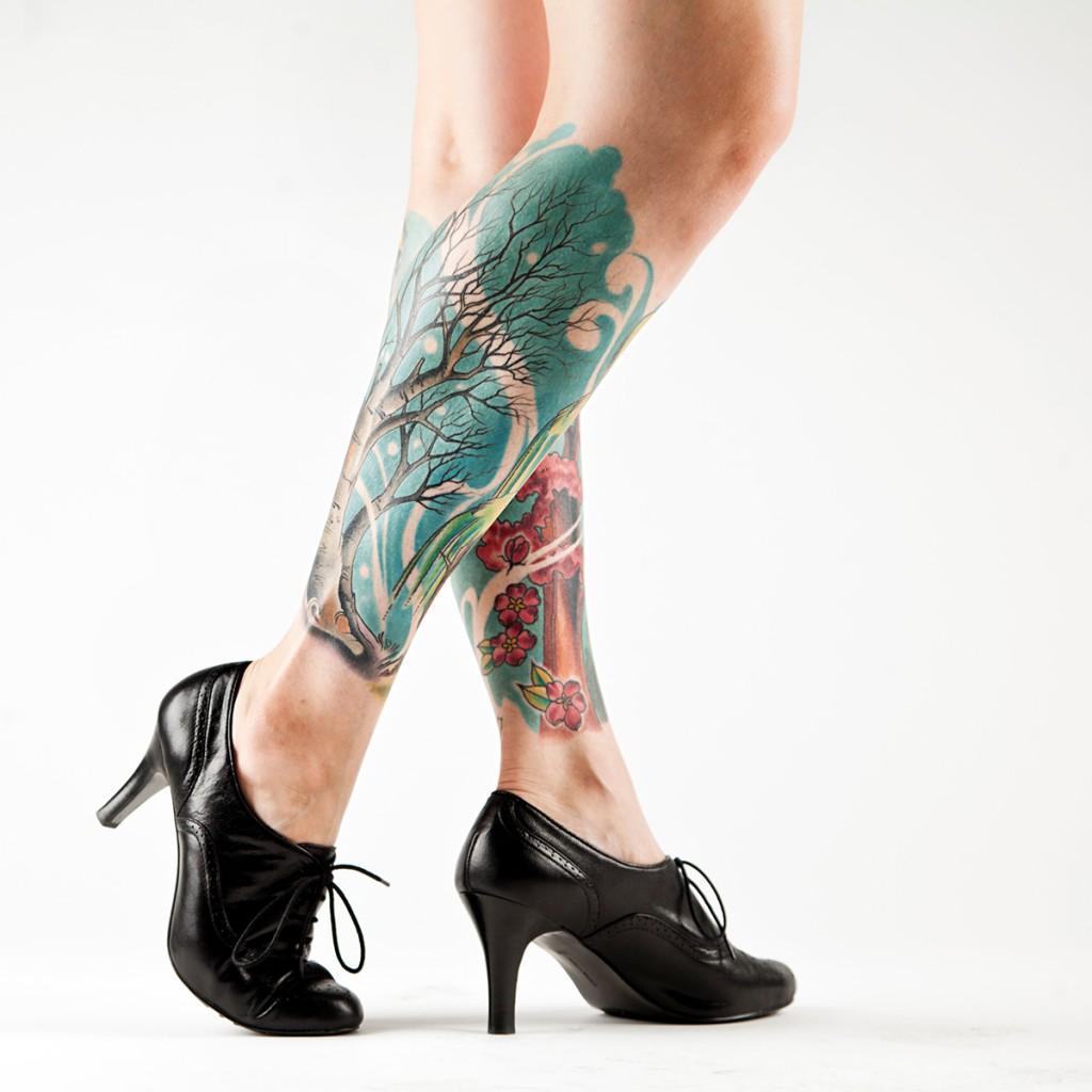 Женская татуировка дерево и сакура на ногах