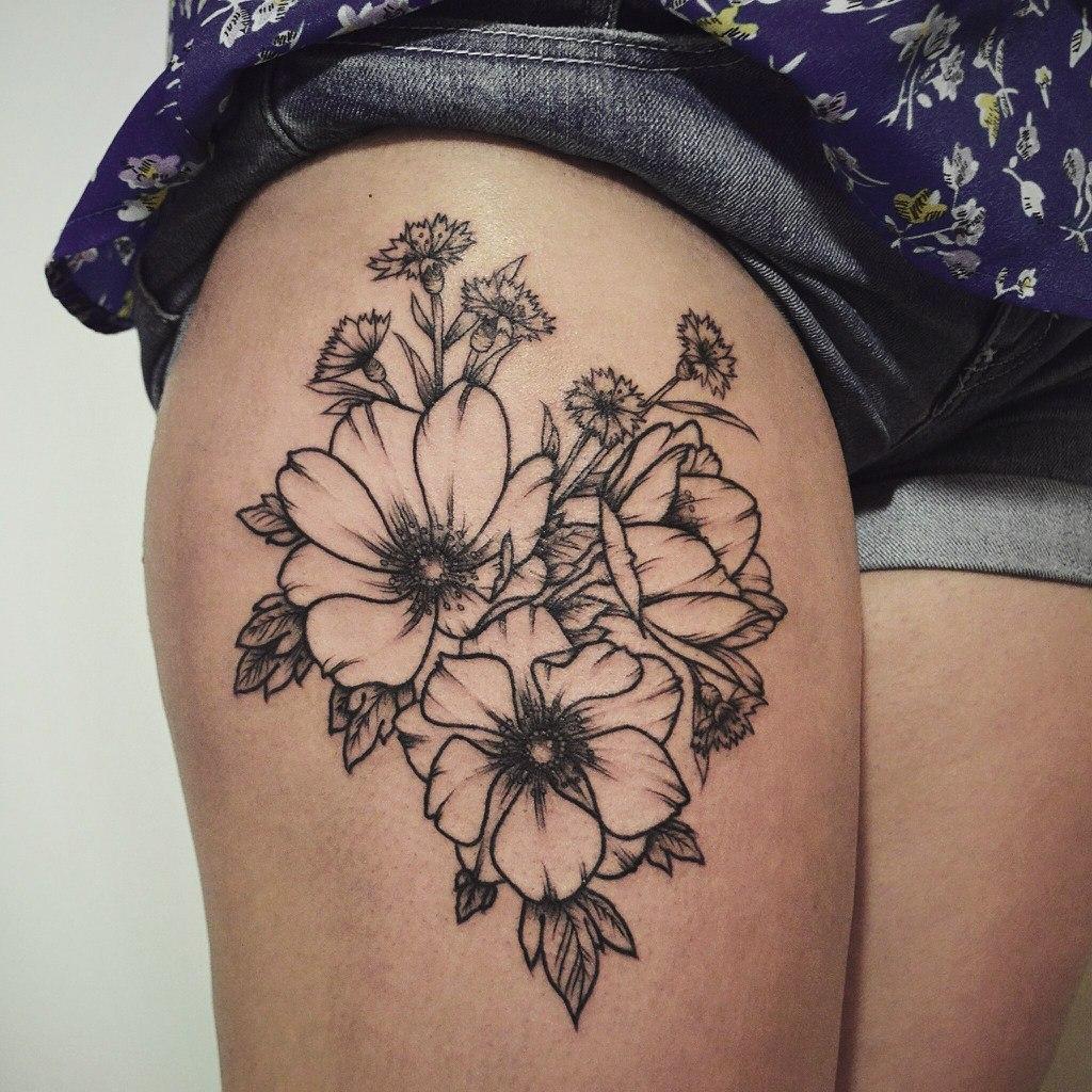 Женская татуировка цветы на бедре