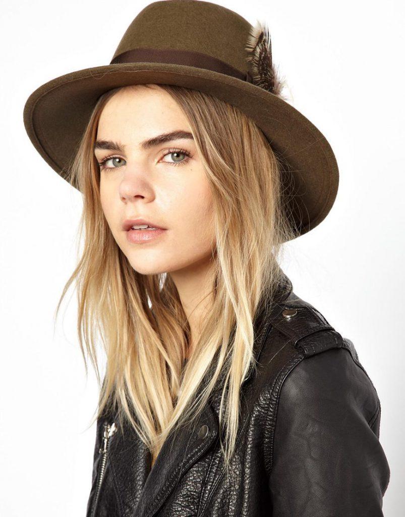 Украшение коричневой фетровой шляпы пером и лентой