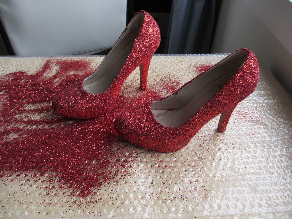 Процесс украшения красных туфель глиттером