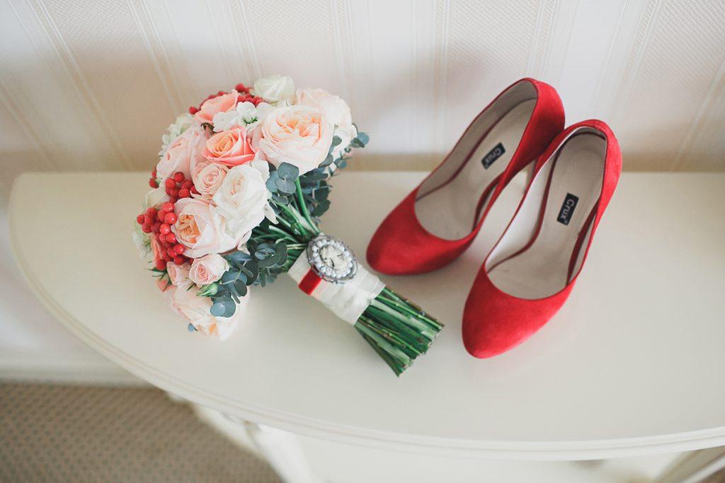 Красные туфли с красивым свадебным букетом