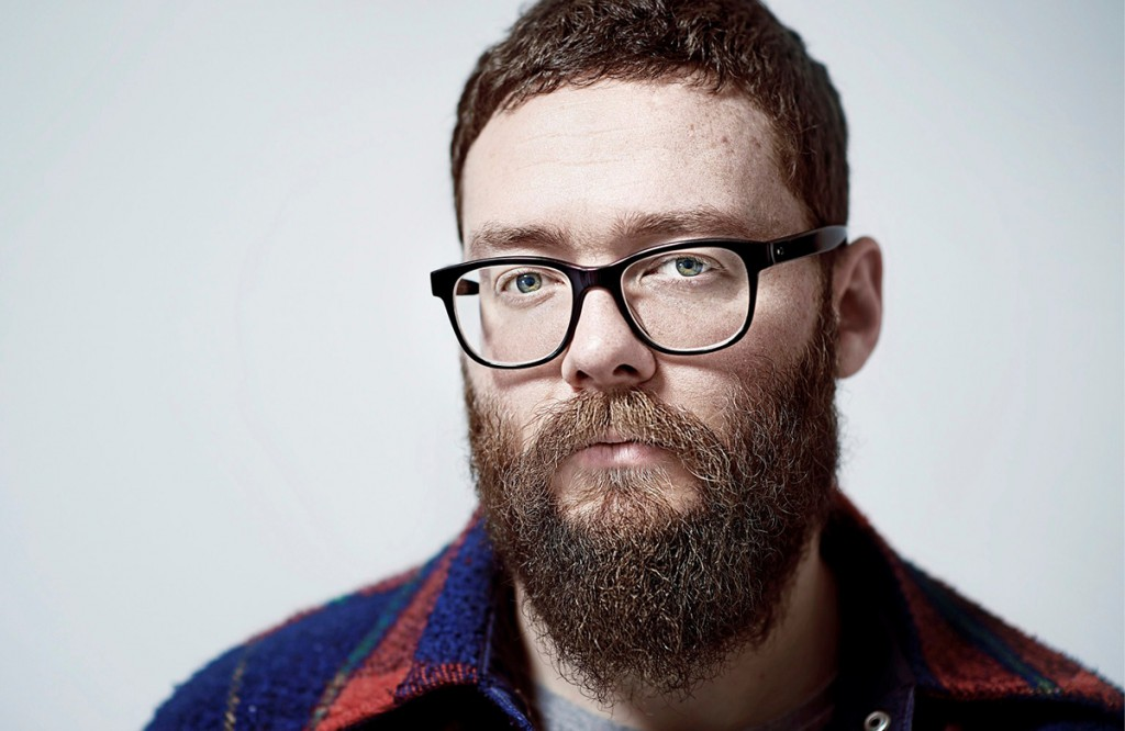 Мужчина с бородой одетый в стиле хипстер в очках