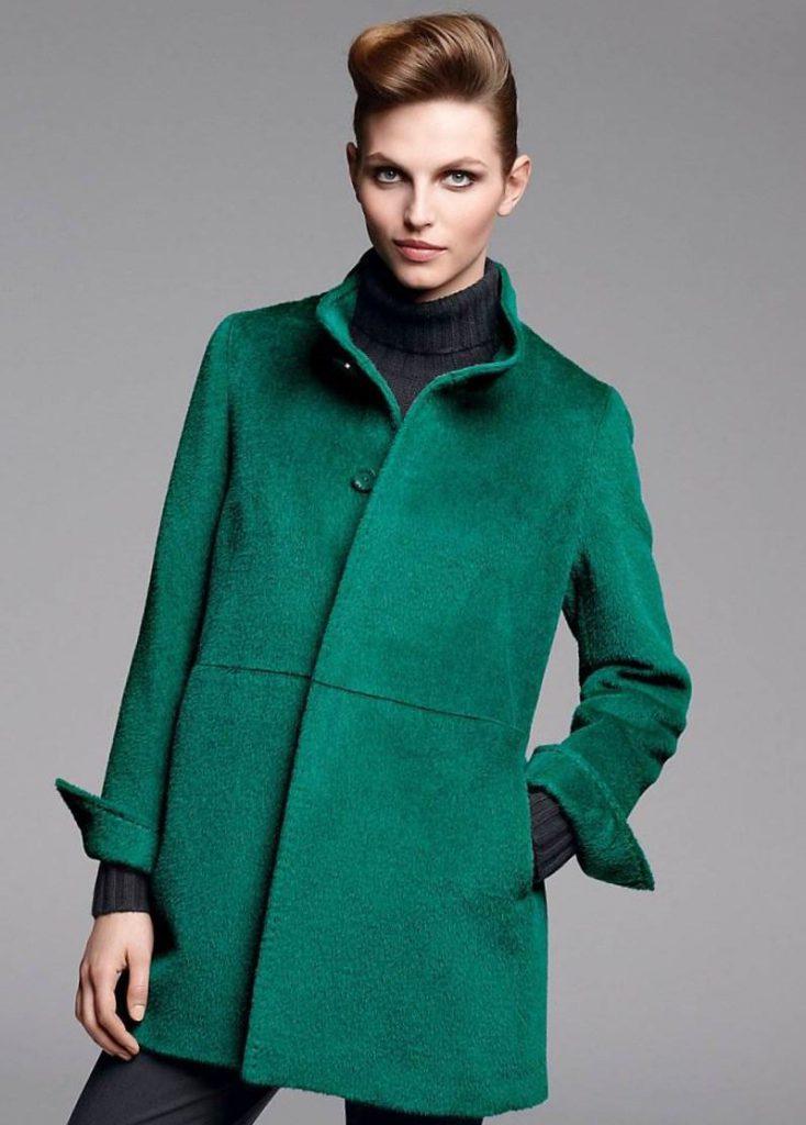 Пальто насыщенного зеленого цвета с черной одеждой