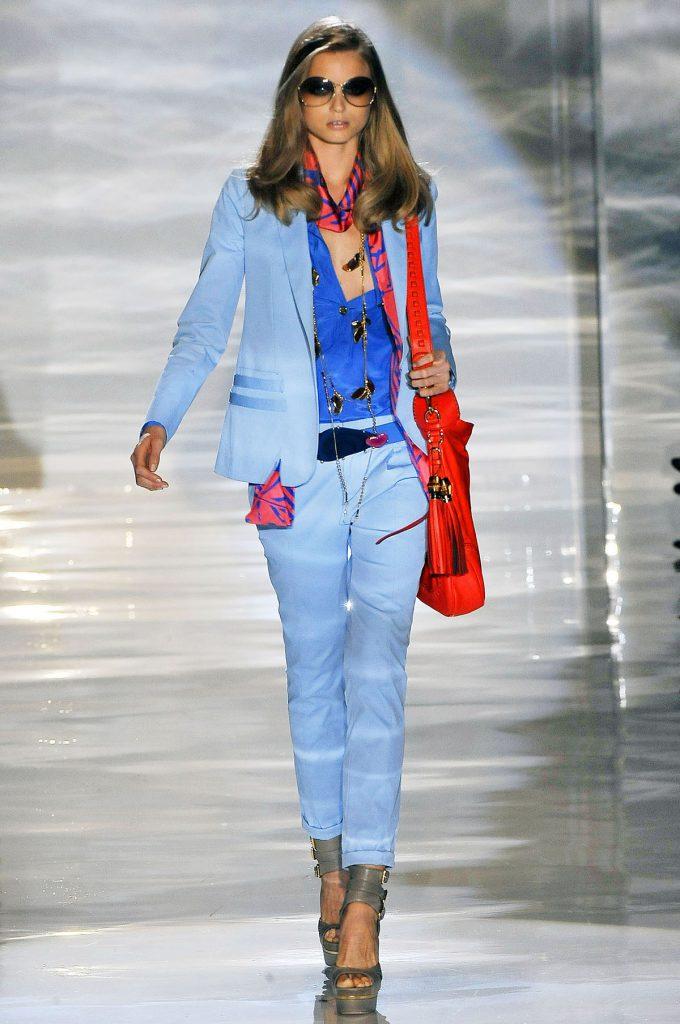 Голубой женский костюм с синей рубашкой и красной сумкой