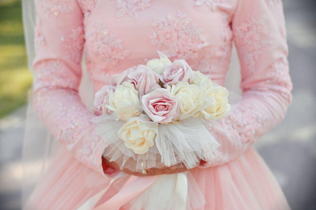 Розовое свадебное платье с красивым букетом