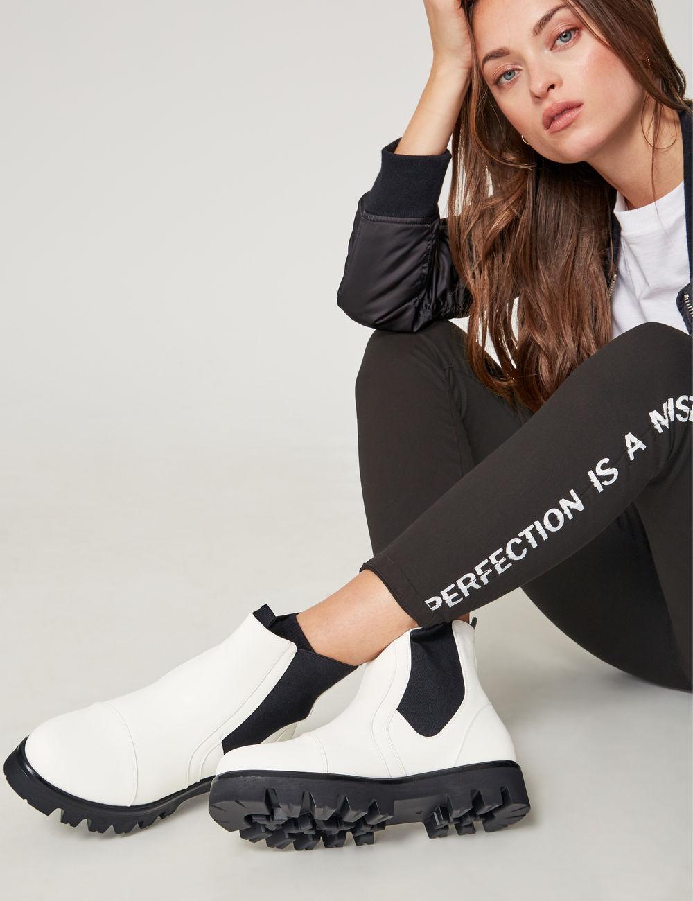 Белые ботинки с черной подошвой